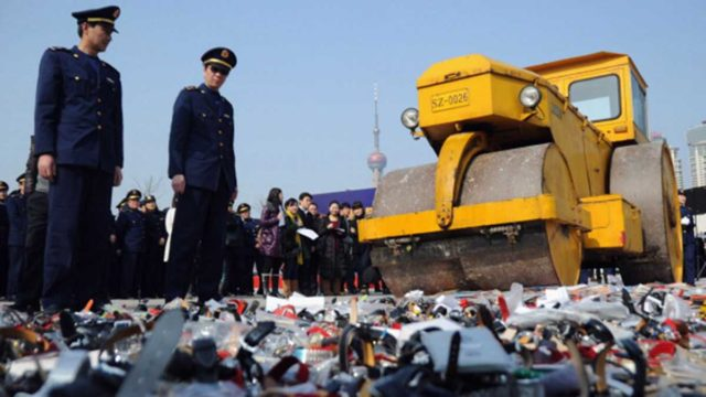Local policemen and members of the public look on as the road roller crushes the counterfeit products in Shanghai.