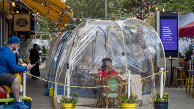 A woman dines in a social distancing bubble at Cafe Du Soleil in New York City as it continues phase 4 of its reopening. The fourth phase allows outdoor arts and entertainment, sporting events without fans and media production (Pic: Getty)